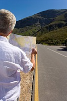 Man looking at map on remote highway