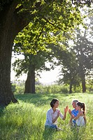 Mothers and daughters playing in field (thumbnail)