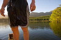 Midsection of man in wet swim trunks