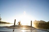 Teenage boy jumping off dock into lake