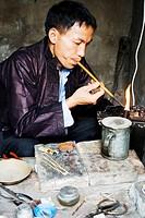 Miao silversmith making silver ornaments using traditional method, Taijiang, Guizhou Province, China