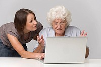 young woman helps older person using laptop