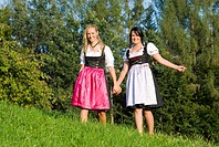 women in dirndl walking in the meadow