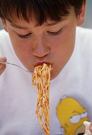 a boy eating spaghetti