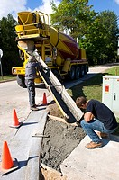 Cement workers work to repair roadway