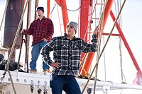 Young fishermen in plaid shirts standing on fishing boat