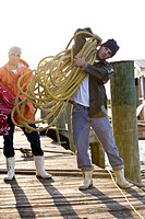 Portrait of fishermen on pier holding ropes and bags