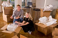 Young couple unpacking moving boxes in new home