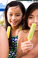 Multi_ethnic children wearing swimsuits eating popsicles