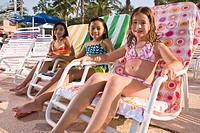 Multi_ethnic girls sitting on deck chairs at water park in summer