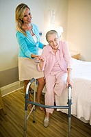 Adult daughter helping elderly mother use walker