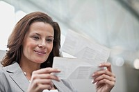 Businesswoman looking at airline tickets