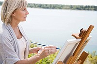 Woman painting along side a lake