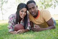 Young couple lying in grass holding football