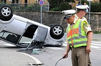 Daihatsu car having rolled over in a traffic accident, lying on its roof, police officer writing up the accident, surveying, Stuttgart, Baden-Wuerttem...