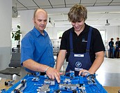 Master, Andreas Fischer, explaining an electric circuit to an apprentice in the BMW training center for automotive mechatronics, Munich, Bavaria, Germ...