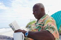 Senior African man reading newspaper at beach