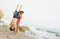 Woman supporting boyfriend doing handstand