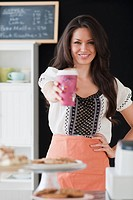 Mixed race woman serving coffee in coffee shop