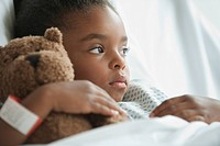Mixed race girl in hospital bed with teddy bear (thumbnail)