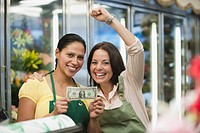 Hispanic women in florist shop holding first dollar bill