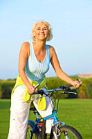 Healthy senior woman riding a bike on a sunny day