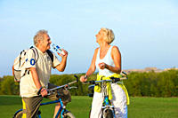 Senior couple riding their bikes on a beautiful day in autumn and drinking water