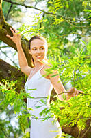 Girl wearing a white dress walking on a branch of a tree in a park