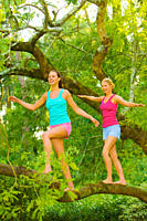 Two young woman balancing on a tree in a park and having fun