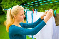 Young woman doing her laundry in the garden and hanging up the clothes to dry