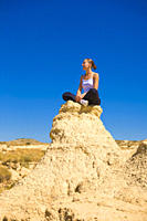 Young woman sitting on a rock in the desert meditating
