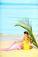 Backview of a young woman at the beach with dolphin and palm branch