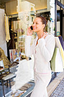 Young business woman shopping in the city and looking through a display window while talking on the phone