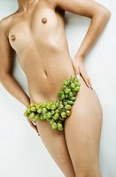 Naked woman with grapes on her hips.
