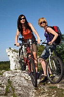 Two woman on bikes on a hill.