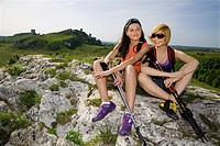 Two women holding ski sticks sitting on a hill.