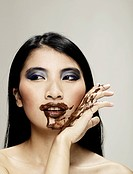 Portrait of a young woman covers herself in chocolate.