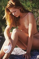 Young woman sitting on a rock, holding a scrubbing brush against her leg (thumbnail)
