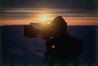 Silhouette of a video photographer during the Sunrise over the icy plains of Baffing Canada