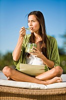 Woman sitting on a mattress and eating bean sprouts (thumbnail)