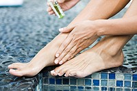 Woman applying oil on her legs at the poolside