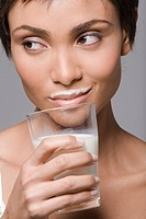 Close_up of a woman drinking milk from a glass