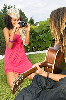 Woman taking a picture of a man playing a guitar