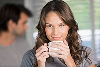 Woman holding a cup of tea and day dreaming