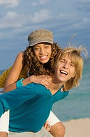 Girl riding piggyback on a teenage boy on the beach