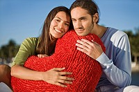 Portrait of a couple hugging a heart shaped cushion