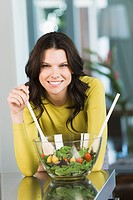 Portrait of a woman mixing salad (thumbnail)
