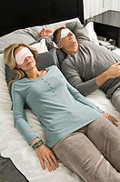 Couple sleeping in bed wearing eye masks