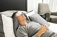 Man sleeping in bed wearing an eye mask
