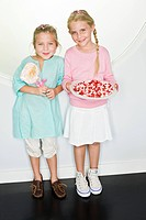 Girl holding a plate of jelly beans with her friend standing beside her